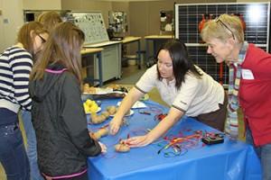 Napavine Elementary teacher Kathleen Krouse looks on while TransAlta's Jennifer  Cerney demonstrates how to make a potato battery